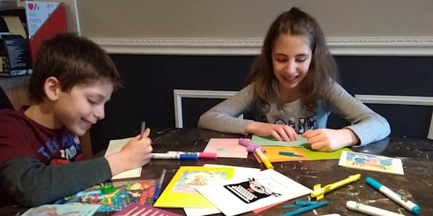 "Jeremy and Tamara Cohn, 10, sign cards for ""The Friend Send."""