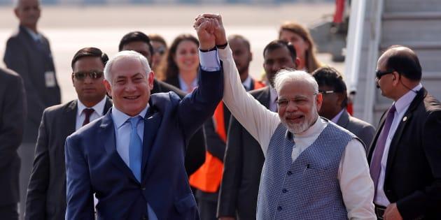 Israeli Prime Minister Benjamin Netanyahu and his Indian counterpart Narendra Modi raise their arms upon Netanyahu's arrival at Air Force Station Palam in New Delhi, India, January 14, 2018.