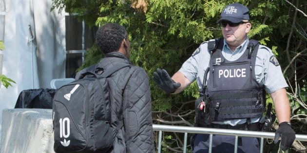 An asylum seeker, claiming to be from Eritrea, is questioned by an RCMP officer as he crosses the border into Canada from the United States on Aug. 21, 2017 near Champlain, N.Y.