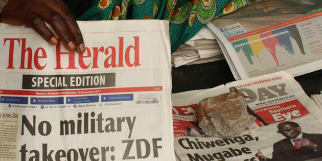 A vendor picks up a copy of a special edition of the state-owned daily newspaper The Herald in Harare, Zimbabwe November 15, 2017.