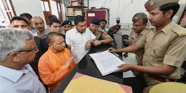 UP Chief Minister Yogi Adityanath speaks to a police personnel during a surprise visit at the Hazratganj police station in Lucknow on 23 March 2017.