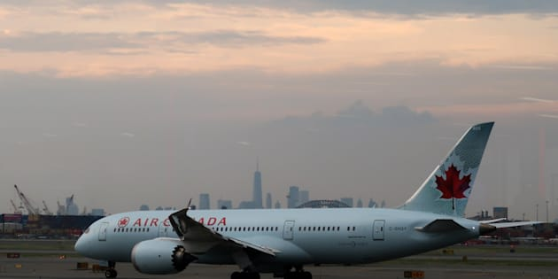 An Air Canada plane passes by the skyline of lower Manhattan in New York City as it taxis to a runway at Newark Liberty Airport on July 20, 2017 in Newark, N.J.