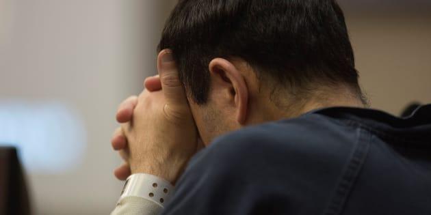 El exmédico de la Federación Estadounidense de Gimnasia, Larry Nassar, se lleva las manos a la cara en el juzgado.