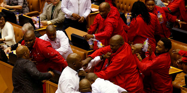 Party leader Julius Malema and members of his Economic Freedom Fighters (EFF) clash with Parliamentary security as they are evicted from the chamber in Cape Town, South Africa, May 17, 2016.  REUTERS/Mike Hutchings