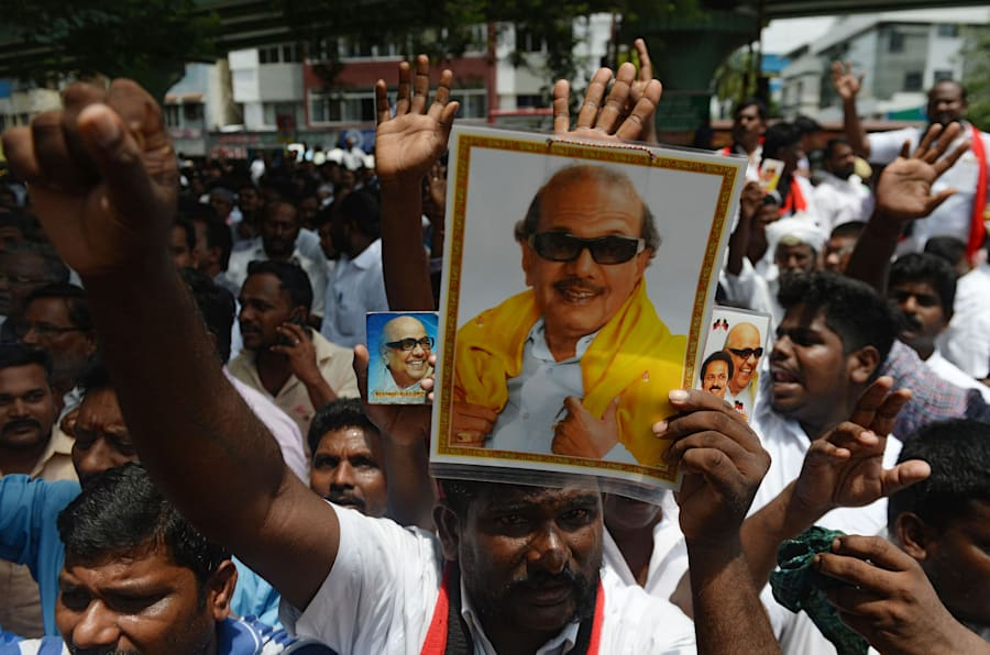 Dravida Munnetra Kazhagam (DMK) party supporters displays portraits of party president M. Karunanidhi in front of the hospital where he is being treated from a urinary tract infection, in Chennai on July 30, 2018.