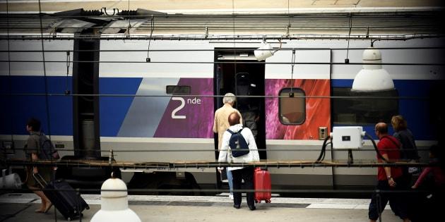 Des voyageurs montent dans un train en gare Montparnasse à Paris, le 1er août.