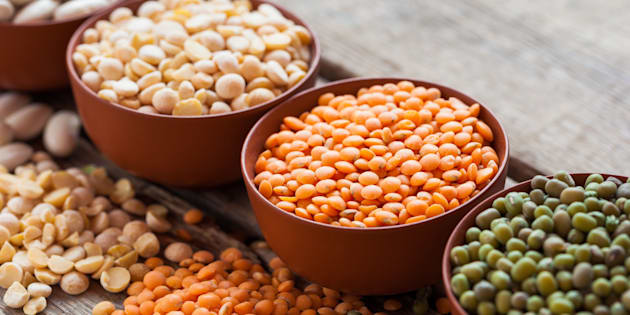 Bowls of cereal grains: red lentils, green mung, corn, beans and peas on wooden kitchen table. Selective focus.