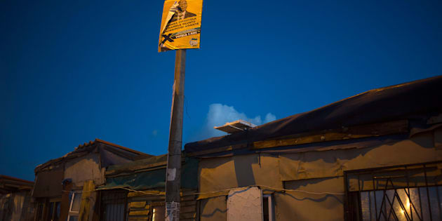 A poster with a photo of South African president, Jacob Zuma hangs over an informal settlement, close to a voting station in Langa, on election day, during the South African local government elections, on August 3, 2016, in Cape Town.
