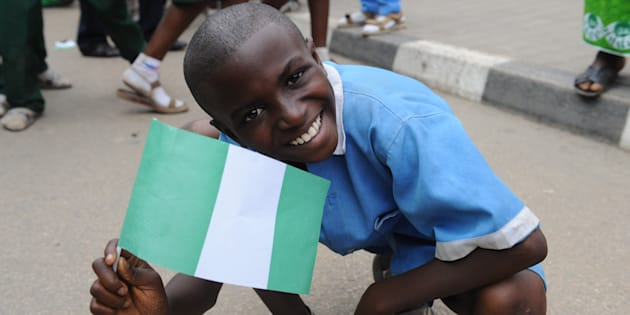 A pupil waves the national flag to welcome the Nigerian football team at the airport in Abuja in February 2013.