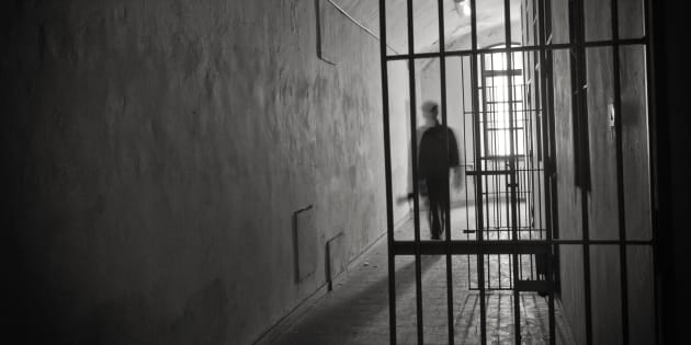 Silhouette of an inmate on prison's cell door.