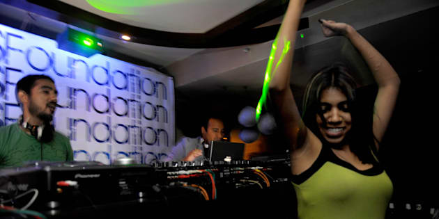 A woman dances as Indian disc-jockeys Nasha (C) and Nucleya (L) play music at a nightclub in New Delhi.
