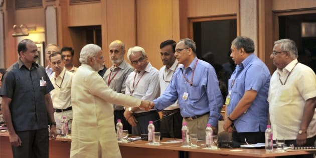 In this June 4, 2014 photo, Indian Prime Minister Narendra Modi, second left in front, interacts with bureaucrats before their meeting in New Delhi, India. The top civil servants in in India's labyrinthine bureaucracy these days, are spending their evenings paging through dictionaries, frantically looking up words. The dictionary searches stem from an order by new Prime Minister Modi: All official work must now be done in Hindi, the language spoken by about 45 percent of India's 1.2 billion people. In a country with as many as 22 official languages many question Hindi's dominance. (AP Photo)