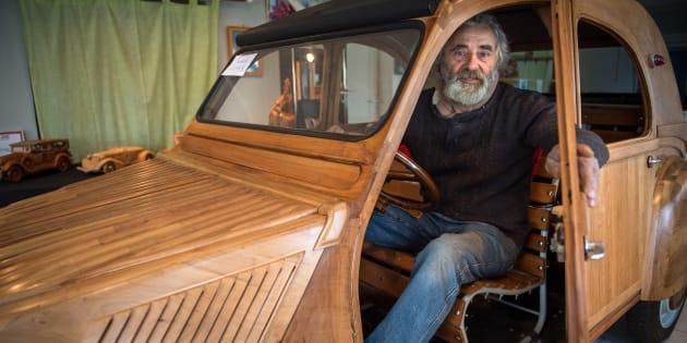 Michel Robillard pose dans sa 2CV construite entièrement à la main et en bois, dans son atelier près de Loches, dans le centre de la France.
