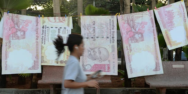 A jogger passes replica prints of the demonetised ₹500 and ₹1,000 notes as part of a street art exhibition in Mumbai. on November 20, 2016.