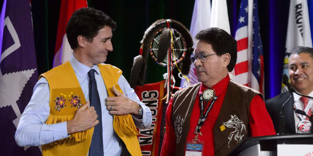 Prime Minister Justin Trudeau is presented with a vest by Mike Mitchell, middle, after addressing the Assembly of First Nations Special Chiefs Assembly in Ottawa on Dec. 4, 2018.