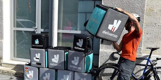 Un coursier de Deliveroo empile des sacs de livraison pour protester contre la modification de leur rémunération.