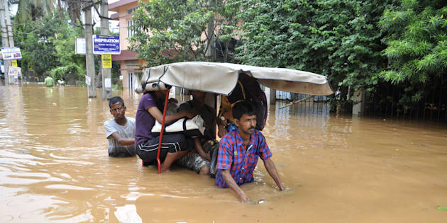 Indian residents navigate floodwaters in the Anilnagar area of Guwahati.