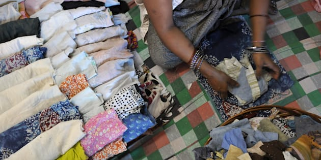 A woman worker making recyclable sanitary cloth napkins at the processing unit of NGO Goonj at Madanpur Kheri on July 1, 2015 in New Delhi, India.