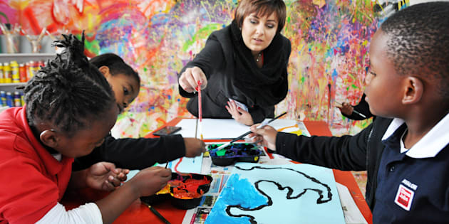A teacher facilitates pupils during a painting session at a newly opened Steve Jobs School on June 23, 2016 in Randburg, South Africa. The schools that cater for children between 2-14 years have two campuses in South Africa. The internationally acclaimed Steve Jobs School model is based on every child having an Independent Learning Plan, centred on their own way of learning, their strengths, preferences and choices.