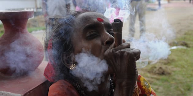 An Indian holy woman smokes marijuana on the eve of the traditional Kharchi Puja festival at Agartala.