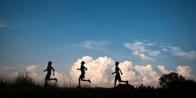 Three boys are running silhouette.