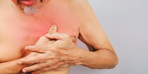 A man clutches his breast area because of pain.
