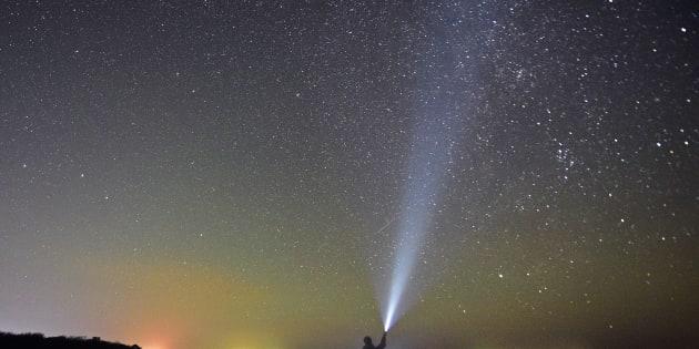 Meteors streak across the night sky during the Orionid meteor shower.