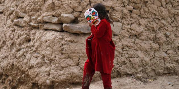 Una niña desplazada en Afganistán con una máscara.