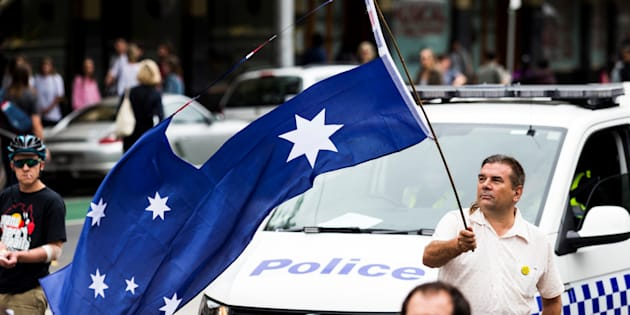 MELBOURNE, AUSTRALIA -- JANUARY 26, 2017: A protestor waves the Australian Flag with the Union Jack removed during a protest, organised by Aboriginal rights activists on Australia Day.
