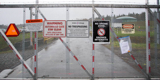Warning signs are displayed on a fence outside of the Kinder Morgan Inc. facility in Burnaby, B.C., Wed. April 11, 2018. Economic damage will extend far beyond the fuel budgets of B.C. residents if Alberta passes and enacts a bill allowing it to restrict exports of oil, natural gas and refined fuels to the province as part of its ongoing pipeline dispute, observers say.