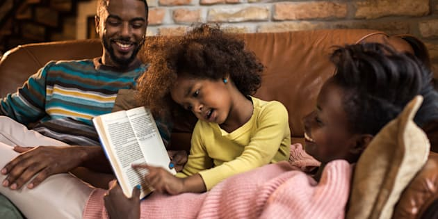 Parents enjoying time with their daughter while she reads to them.