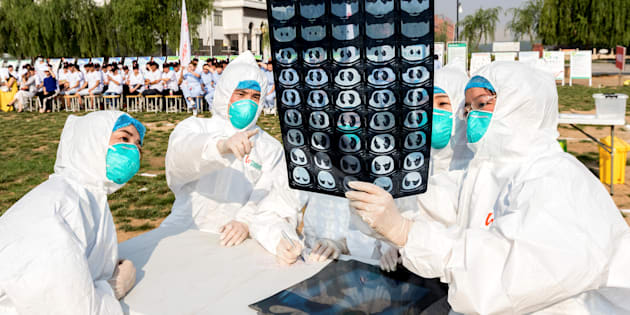 People participate in an emergency exercise on prevention and control of H7N9 bird flu virus organised by the Health and Family Planning Commission of the local government in Hebi, Henan province, China.