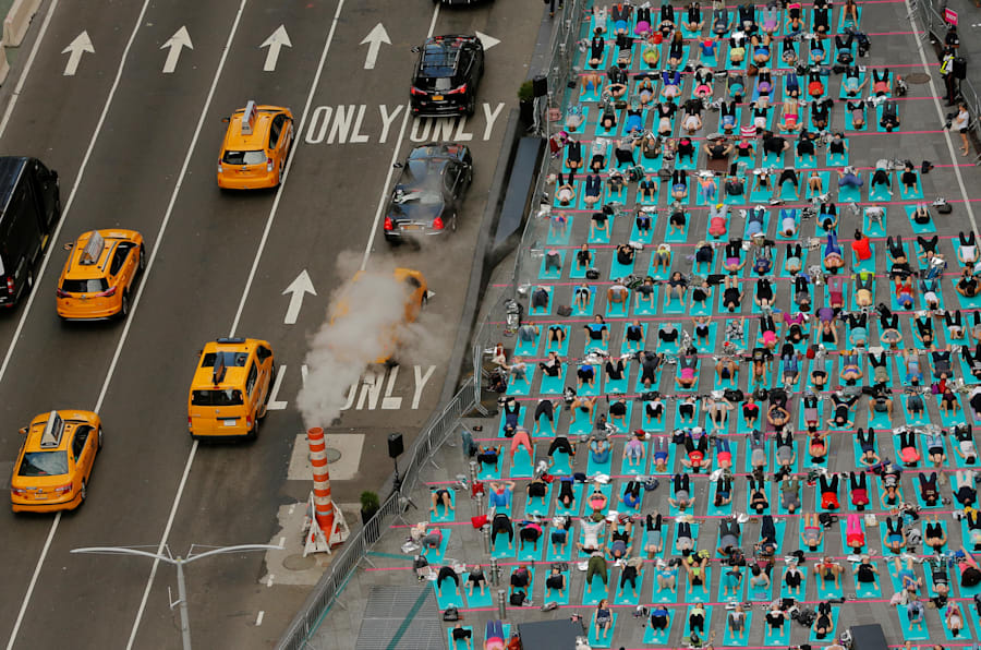 People participate in a yoga class during an annual Solstice event in the Times Square district of New York, U.S., June 21, 2017. REUTERS/Lucas Jackson      TPX IMAGES OF THE DAY