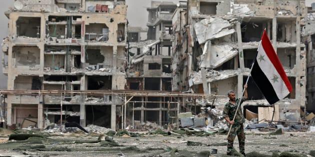 Un membre des forces pro-gouvernementales syriennes devant des bâtiments endommagés dans le camp de réfugiés palestiniens de Yarmouk, à la périphérie sud de Damas, le 22 mai 2018.