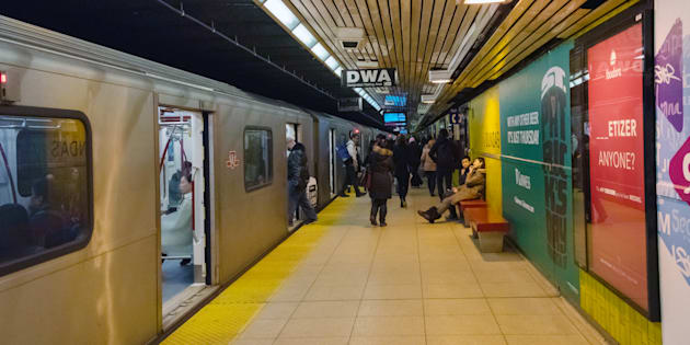 Transit users board and exit a Toronto Transit Commission subway train.