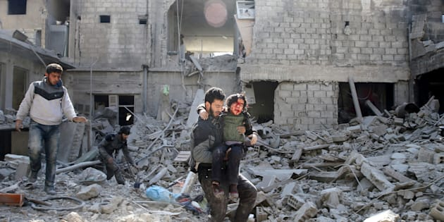 A man carries an injured boy as he walks on rubble of damaged buildings in the rebel held besieged town of Hamouriyeh, eastern Ghouta, near Damascus, Syria, February 21, 2018.