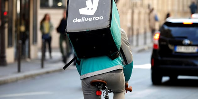 A cyclist rides a bicyle as he delivers food for Deliveroo.