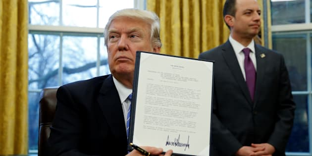 U.S. President Donald Trump holds up the executive order on the reinstatement of the Mexico City Policy after signing in the Oval Office of the White House in Washington January 23, 2017.