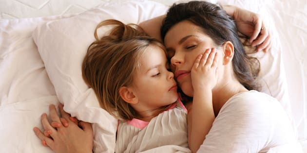 Mother with her daughter  slipping in bed.