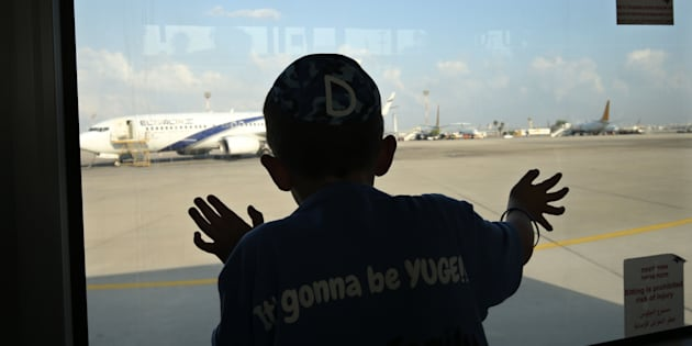 TOPSHOT - A child looks through the window of a bus as Jewish immigrants from the US, making Aliyah (Immigration to Israel), arrive at the Ben Gurion International Airport near Tel Aviv on August 17, 2016. / AFP / GALI TIBBON        (Photo credit should read GALI TIBBON/AFP/Getty Images)