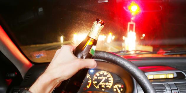 Un conductor lleva una cerveza mientras circula por la carretera.