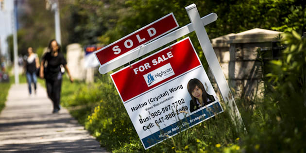 "A woman walks towards a ""for sale"" sign of a home that has been sold in Toronto, June 29, 2015."