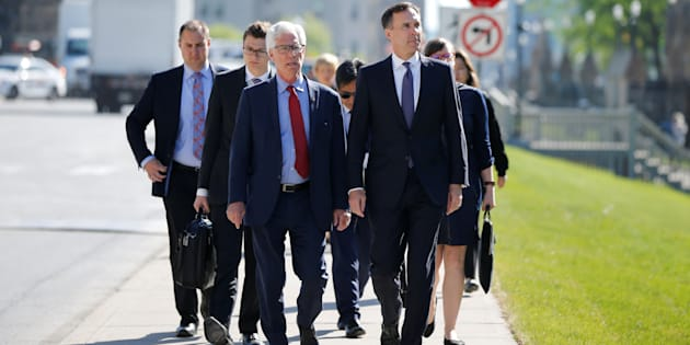 Finance Minister Bill Morneau (right) and Natural Resources Minister Jim Carr walk to a news conference to make an announcement about the Kinder Morgan Trans-Mountain pipeline, Ottawa, May 29, 2018. Industry analysts and climate groups agree on at least one thing: The political battle over the expansion of the contentious pipeline is not over.