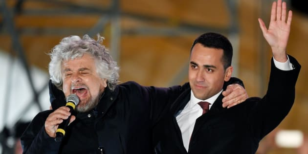 Italy's populist Five Star Movement (M5S) founder Beppe Grillo and M5s leader Luigi Di Maio (R) hug at the end of the last election campaign meeting in Piazza del Popolo square in Rome on March 2, 2018.