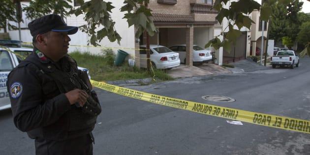 Un policía monta guardia fuera de la casa donde se encontró el cadáver de la periodista Alicia Díaz González, que trabajaba para el periódico El Financiero.