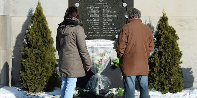 People stop at the memorial plaque in honour of the 13 students and one staff member killed in the Polytechnique massacre in Montreal on Dec. 6, 2016.