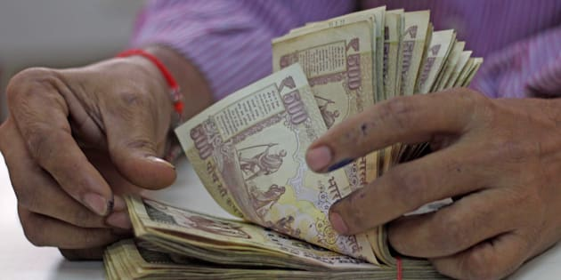 A man counts old 500 and 1000 notes inside the bank at Vashi, on November 21, 2016 in Mumbai, India.