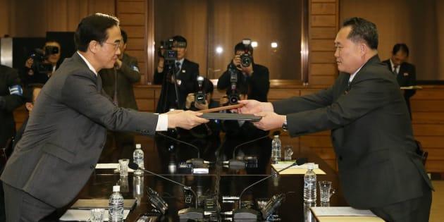 El ministro de Unificación surcoreano, Cho Myoung-gyon (izquierda), y el jefe de la Agencia Norcoreana para Asuntos con el Sur, Ri Son-gwon, se intercambian una declaración conjunta tras su reunión de hoy.