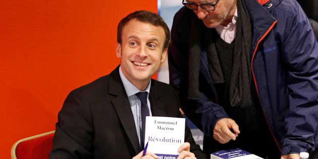 """Emmanuel Macron présentant dédicaçant son livre """"Révolution"""" à Paris le 24 novembre 2016."""