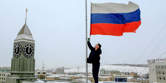 A worker lowers the Russian national flag to half-mast on a roof of the city administration building, as the country observes a day of mourning for victims of the Tu-154 plane which crashed into the Black Sea on its way to Syria on Sunday, in Krasnoyarsk, Russia, December 26, 2016.  REUTERS/Ilya Naymushin     TPX IMAGES OF THE DAY
